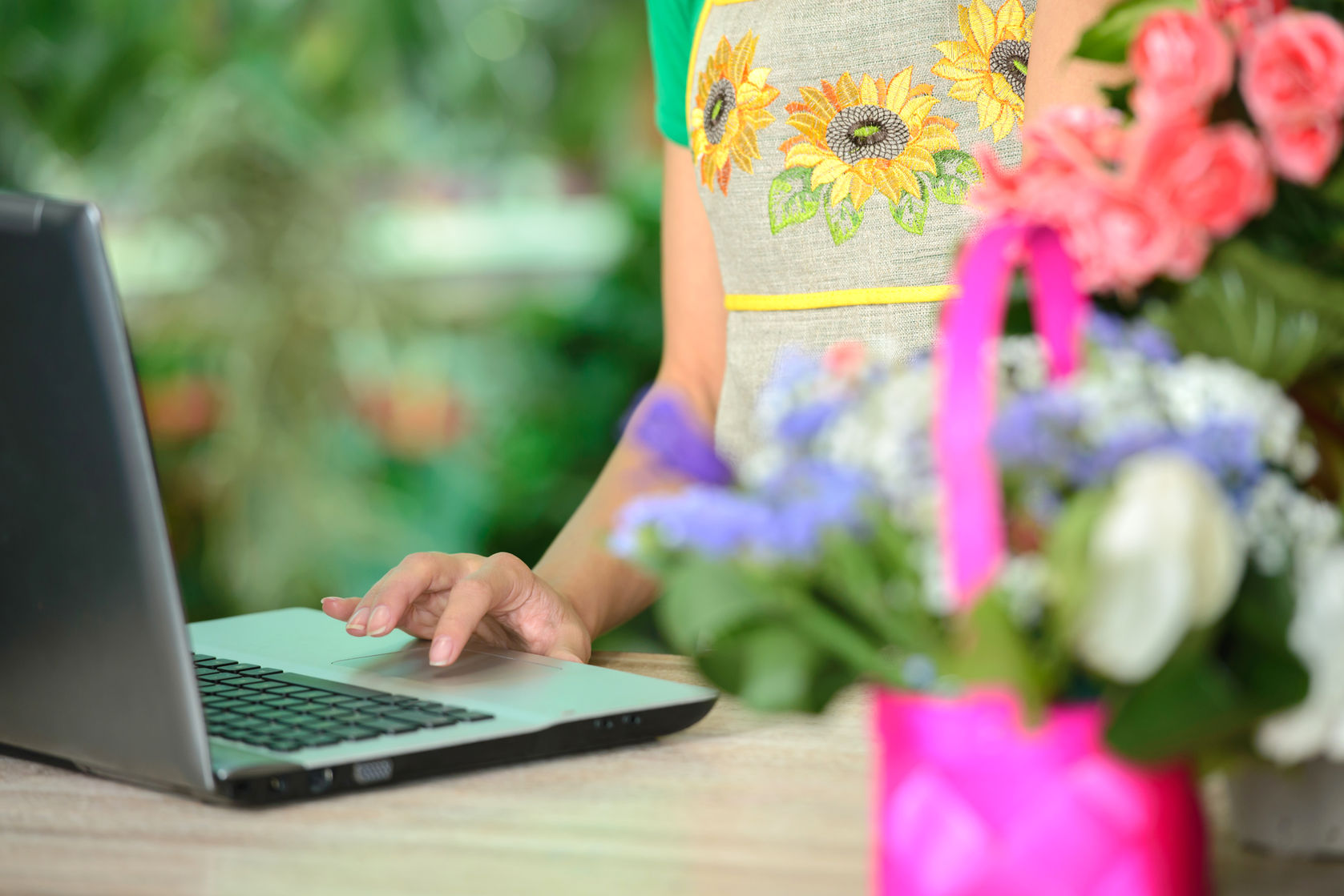 31991698 - portrait of an attractive florist business woman owner sitting at a flower shop counter using a laptop computer to place a stock order on line. small business technology.